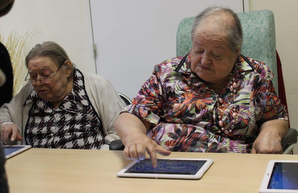 deux personnes agées utilisant des tablettes